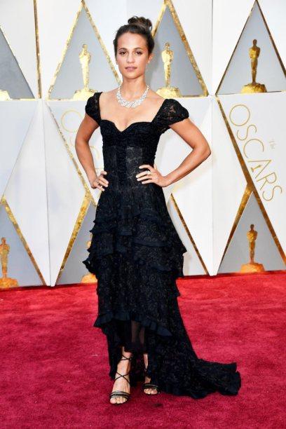 Felicia Vikander parace que acabou de sair de um cabaret com este vestido de corpete. A renda até acho engraçado mas fica só por aí. Além disso o bun simples que tem como penteado parece o mesmo que faço quando estou a arrumar a casa ou então a ir para o ginásio.