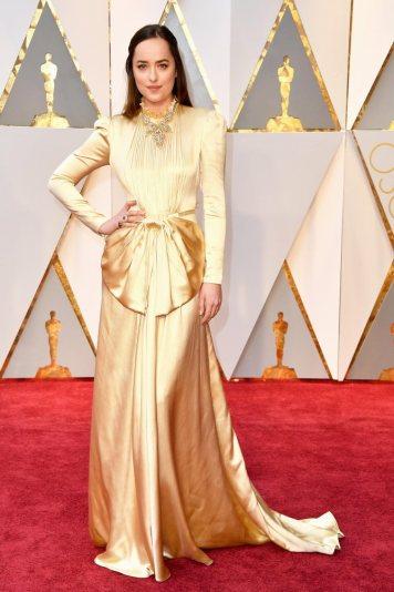 """A Dakota Johnson cansou de mostrar pele nos dois filmes de """"50 Sombras de Grey"""" que se tapou toda neste vestido que roubou à avó. Oh filhinha não é nada que ainda não tenhamos visto."""