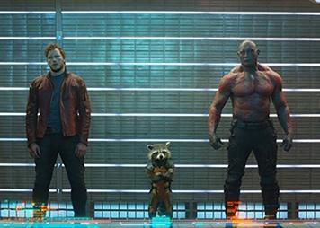 """Em """"Guardiões da Galáxia"""" (2014) conhecemos a equipa de Star-Lord (Chris Pratt), a Gamora (Zoe Saldana), o Drax (Dave Bautista), o Rocket (Bradley Cooper) e o Groot (Vin Diesel). Um grupo criminosos intergalácticos com um humor muito aguçado e sem nada a perder que se conhecem numa prisão. Juntos vão evitar que um guerreiro fanático controle o universo. A parte mais importante do filme é a Pedra do Poder. Os Guardiões da Galáxia terão de a proteger das mãos do inimigo Ronan e principalmente de Thanos. Na cena pós-créditos o """"Colecionador"""" volta a aparecer. O seu espaço de relíquias está completamente destruído, só pode significar que a Pedra do Infinito foi roubada"""