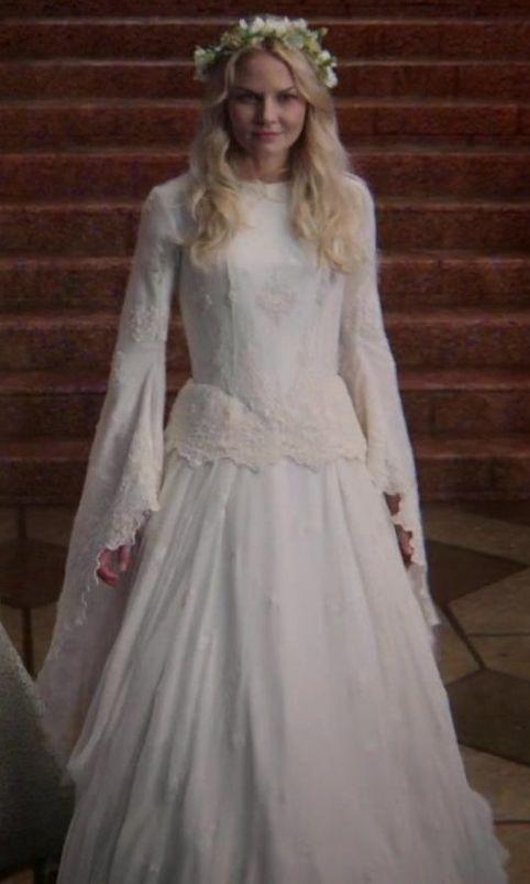 Emma com um vestido singelo branco com rendas e coroa de flores. Muito angelical e adoro aquelas mangas.